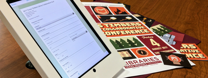 The registration site displayed on an ipad in front of the event poster.
